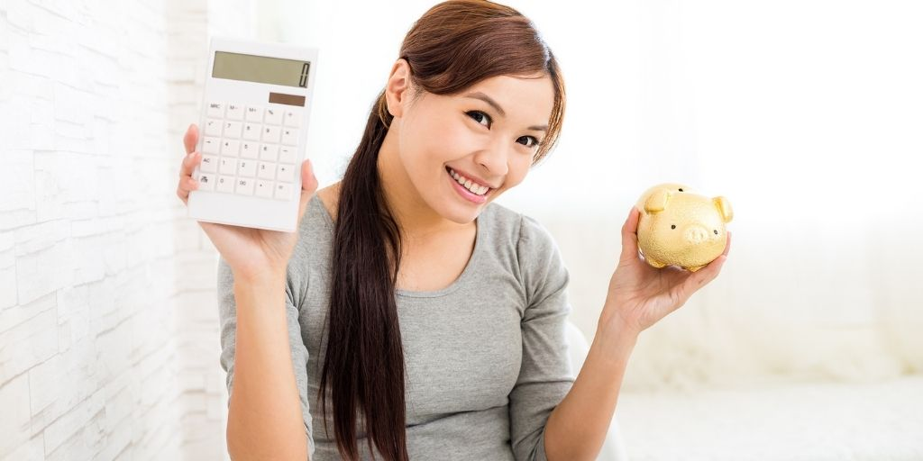 young woman smiling, holding calculator and piggy bank to track her money saving goal