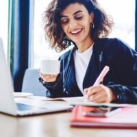 middle aged woman smiling with coffee working on steps to achieve savings goal at desk