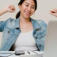 young woman at computer in jean shirt, excited about no longer being bad with money