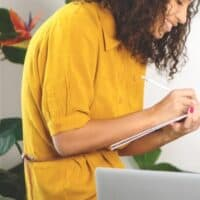 woman in yellow shirt taking notes about managing her money effectively