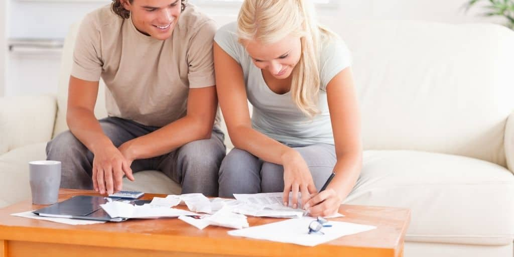 young couple working on printable for how to get one month ahead on bills, smiling