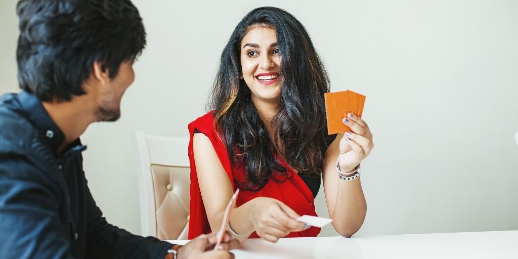 couple smiling at one another, playing with deck of conversation starters for married couples