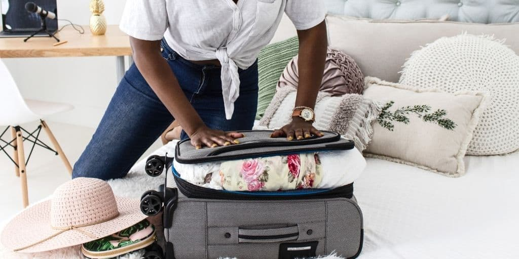 woman trying to zipper up an overfilled suitcase on the bed