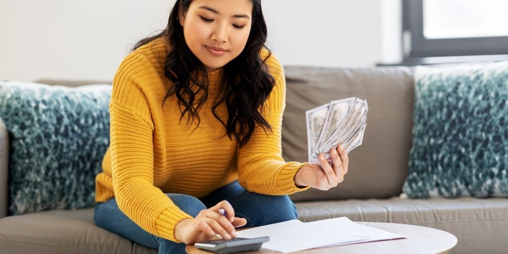 young woman in orange sweater with money calculating daily money saving challenge amount