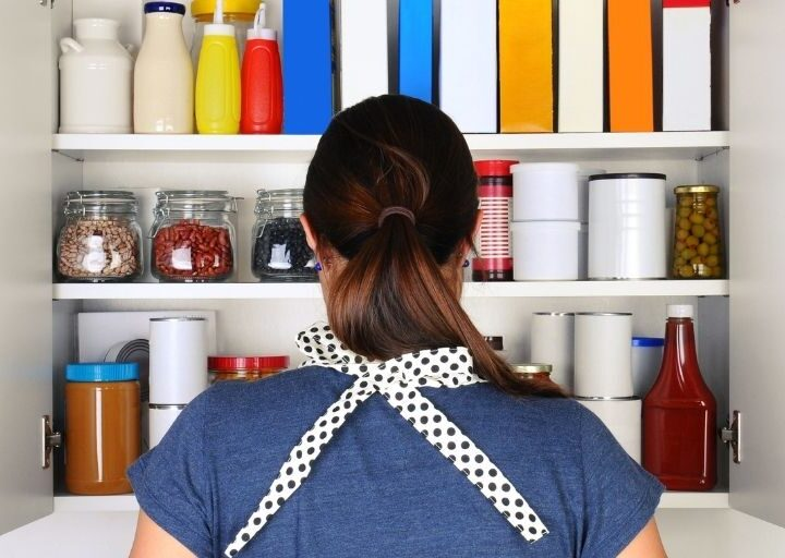 woman facing pantry wide open, trying to figure out what to cook